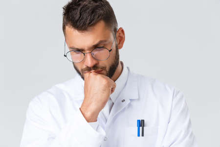 Healthcare workers, coronavirus, covid-19 pandemic and insurance concept. Close-up of concerned young doctor thinking about problem, treating sick patients, look down thoughtful, making choice