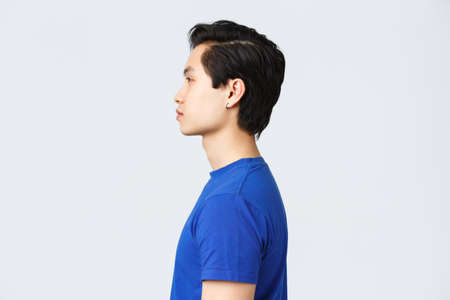 Lifestyle, people emotions and beauty concept. Profile portrait of stylish good-looking asian hipster, queer guy with earring, new haircut from barbershop, look normal expression left