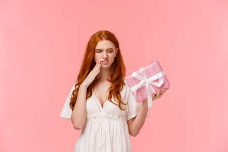 Picky and ignorant displeased spoilt redhead girl, holding wrapped cute box with gift, looking with scorn and disappointment at present, grimacing, cringe displeased, dislike it Stock Photo