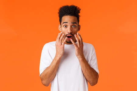 Scared, freaked-out and shocked african-american young hipster guy looking at something scary or frightening, standing concerned over orange background, hold hands near opened mouth