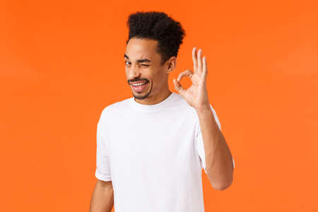 Rely on me. Outgoing relaxed and confident young attractive african-american male encourage, being assertive, showing okay sign and wink, reassure all is good, orange background