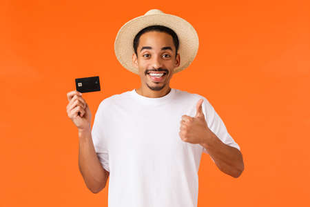 Waist-up portrait attractive smiling african american male tourist using bank service abroad, showing thumb-up and grinning approval, holding credit card, recommend payment method, orange background