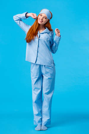 Full-length vertical shot cute and silly, teenage redhead girl, wearing lovely pyjama, waking up and stretching, had good sleep, smiling in morning, standing pleased blue background