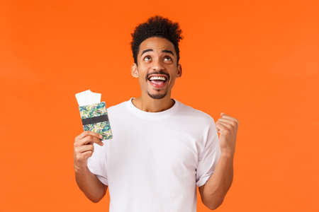 Celebration, prize or achievement concept. Attractive african-american man finally having vacation, fist pump, thank god, look camera happy, holding passport with two tickets, orange background