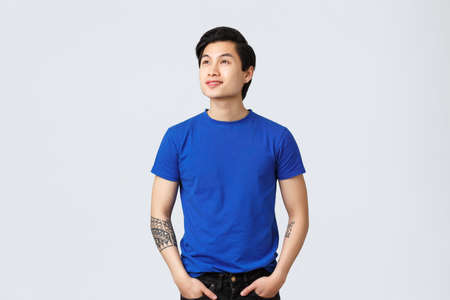 Dreamy, thoughtful handsome asian queer guy in blue t-shirt, looking forward something, gazing at upper left corner with delighted, smiling face, reading banner or promo, grey background