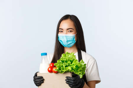 Covid-19, grocery store, employment, small business and preventing virus concept. Smiling cute asian female shop worker, cashier in medical mask and gloves taking care of your groceries order