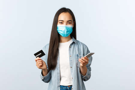 Social distancing lifestyle, covid-19 pandemic and contactless shopping concept. Pretty smiling asian female in medical mask, paying for online order using mobile phone and credit card