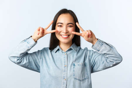 Lifestyle, people emotions and beauty concept. Close-up of cheerful smiling asian girl showing v-sign peace over eyes, standing kawaii pose, feeling carefree and upbeat