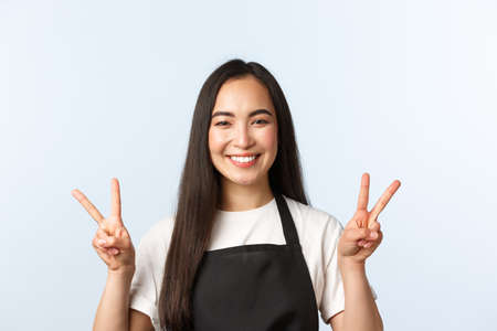 Coffee shop, small business and startup concept. Close-up of cheerful asian female barista, shop or cafe worker in medical mask, smiling upbeat and show peace v-signs, white background