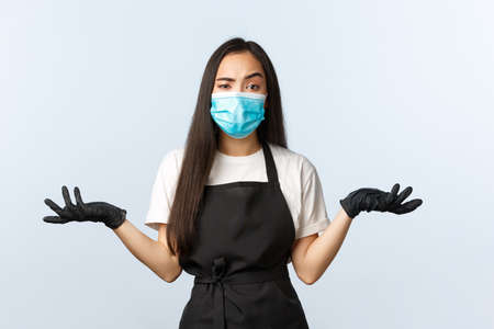 Covid-19, social distancing, small coffee shop business and preventing virus concept. Confused and annoyed asian employee, barista in medical mask and gloves shrugging with spread hands sideways