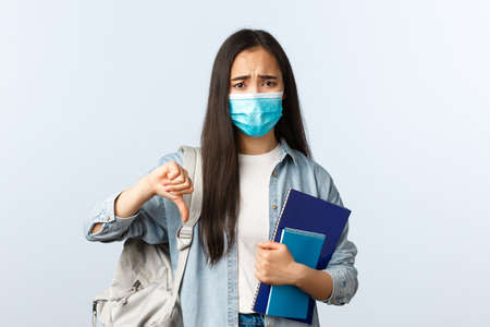 Covid-19 pandemic, education during coronavirus, back to school concept. Upset and disappointed freshman student in medical mask complaining, holding notebooks and thumb-down Imagens
