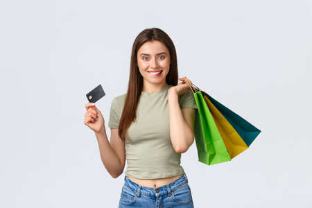 Shopping mall, lifestyle and fashion concept. Excited smiling young woman biting lip, tempt to waste all money on credit card, holding bags with clothes and looking pleased, white background