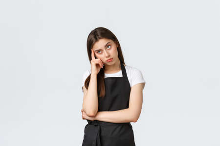 Grocery store employees, small business and coffee shops concept. Annoyed tired saleswoman fed up listening to lame story. Female barista eye roll bothered at camera, white background