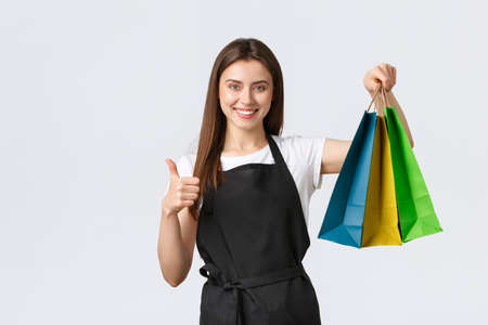 Grocery store employees, business and coffee shops concept. Cute confident smiling saleswoman in black apron showing thumbs-up, guarantee quality of purchased items, holding paper bags with goods