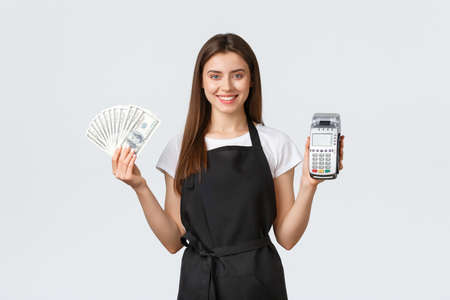 Grocery store employees, small business and coffee shops concept. Cheerful pretty female barista, cafe worker in black apron showing two ways of easy payment, POS terminal and cash