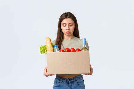 Online home delivery, internet orders and grocery shopping concept. Disappointed female customer receive wrong order of groceries, looking upset inside box and pouting, stand white background