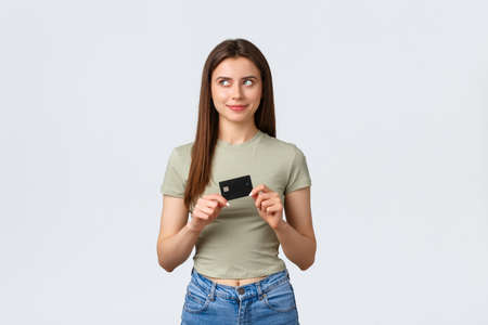 Shopping mall, lifestyle and fashion concept. Thoughtful pleased female thinking what buy on all money bank account, looking left with pleased smile and holding credit card
