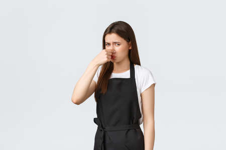 Grocery store employees, small business and coffee shops concept. Displeased and bothered female barista shut nose and grimacing from awful smell, something rot in kitchen
