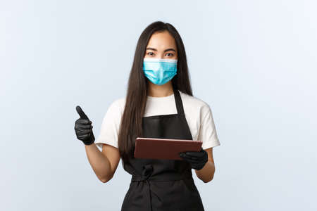 Covid-19, online orders, small coffee shop business and preventing virus concept. Smiling cute asian female barista in apron, medical mask and gloves, show thumb-up, take order with digital tablet