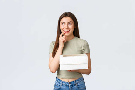 Delivery, lifestyle and food concept. Dreamy happy stylish woman looking up thoughtful, smiling as imaging something, holding box with desserts, delicious food order, stand white background