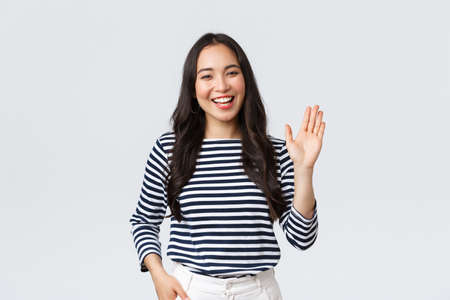 Lifestyle, people emotions and casual concept. Friendly cheerful asian woman smiling, saying hi and waving hand to greet person, make hello gesture, welcome someone Banco de Imagens - 150087023