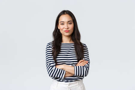 Lifestyle, beauty and fashion, people emotions concept. Skeptical and judgemental asian female office manager looking picky, smirk and pouting dissatisfied, cross arms chest Stock Photo