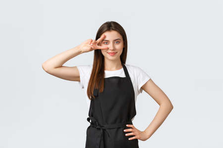 Grocery store employees, small business and coffee shops concept. Optimistic friendly cute barista in black apron show peace sign over eye and smiling, inviting visitors to cafe or restaurant