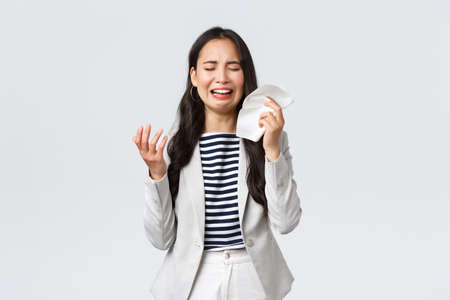 Business, finance and employment, female successful entrepreneurs concept. Uneasy distressed asian office lady feeling sad, crying and sobbing, wipe tears with tissue, complaining