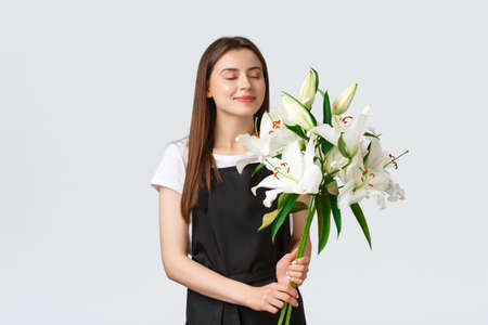 Shopping, employees and small business concept. Smiling dreamy female florist in flower shop close eyes and sniffing nice smell of white lilies bouquet, white background