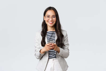 Business, finance and employment, female successful entrepreneurs concept. Smiling pleasant asian businesswoman, real estate broker wear glasses, using mobile phone to contact clients