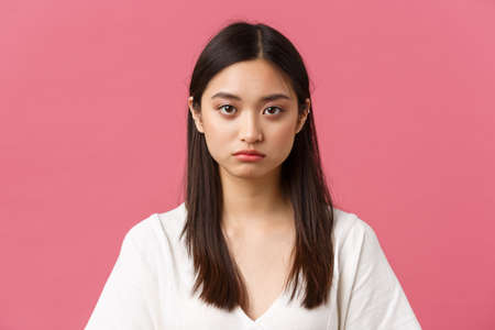 Beauty, people emotions and summer leisure concept. Close-up of gloomy and sad, tired young asian female employee looking at camera reluctant, standing distressed over pink background Stock Photo