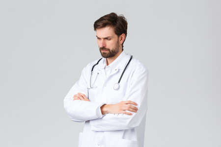 Hospital, healthcare workers, covid-19 treatment concept. Troubled serious-looking, concerned doctor in scrubs, facing difficult decision, solving troublesome case, frowning pondering