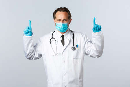 Covid-19, preventing virus, healthcare workers and vaccination concept. Serious mad doctor in medical mask and gloves pointing fingers up disappointed, explain measures how fight disease