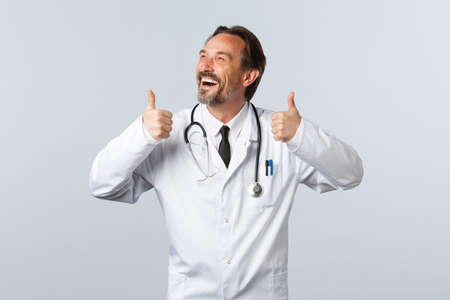 Covid-19, coronavirus outbreak, healthcare workers and pandemic concept. Carefree happy male doctor in white coat, looking upper left corner and laughing show thumbs-up in approval