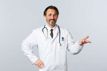 Covid-19, coronavirus outbreak, healthcare workers and pandemic concept. Skeptical and confused male doctor in white coat, pointing right with dismay or irony, grimacing disappointed
