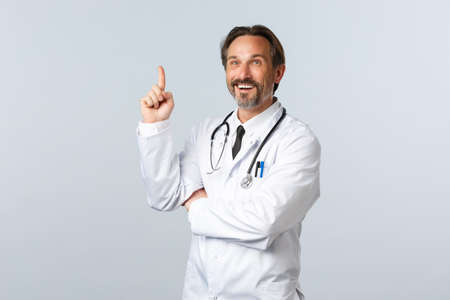 Covid-19, coronavirus outbreak, healthcare workers and pandemic concept. Pleased excited smiling doctor raise index finger as have great idea, solved case, standing white background