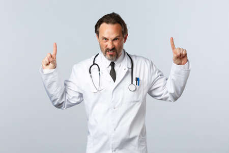 Covid-19, coronavirus outbreak, healthcare workers and pandemic concept. Angry outraged male doctor in white coat, pointing fingers up grimacing furious, looking mad at camera, white background