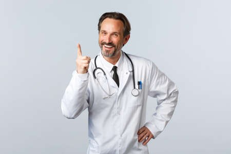 Covid-19, coronavirus outbreak, healthcare workers and pandemic concept. Well played, nice work. Cheerful male doctor in white coat shaking finger and laughing as scolding someone