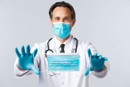 Covid-19, virus, healthcare workers and vaccination concept. Doctor in PPE extend hands and give patient medical mask, recommend using preventing measures against coronavirus disesase
