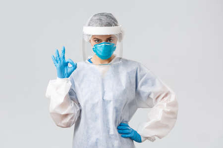 Covid-19, preventing virus, health, healthcare workers and quarantine concept. Serious doctor, professional nurse in PPE, protective suit, respirator and gloves, make okay sign, guarantee