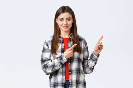 Lifestyle, different emotions, leisure activities concept. Determined smiling female student pointing fingers upper right corner, inform freshman new opportunities, educational program