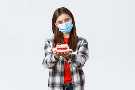 Coronavirus outbreak, lifestyle during social distancing and holidays celebration concept. Tender caring girlfriend made homemade cake, giving it to you, wear medical mask and smiling