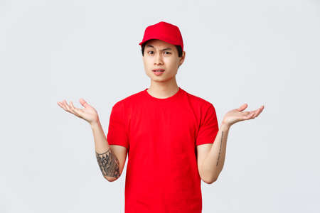 Express delivery, shipping and logistics concept. Courier dont understand why, wearing red cap and t-shirt, shrugging with hands spread sideways, grimacing bothered, complain Reklamní fotografie