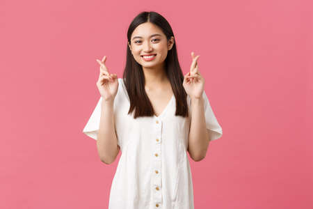 Beauty, people emotions and summer leisure concept. Optimistic asian girl having faith in dreams come true, cross fingers good luck and smiling happy camera, believe over pink background Foto de archivo - 150562387