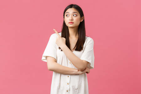 Beauty, people emotions and summer leisure concept. Doubtful and curious cute asian girl in dress, looking and pointing upper left corner with hesitant expression, pink background Stok Fotoğraf