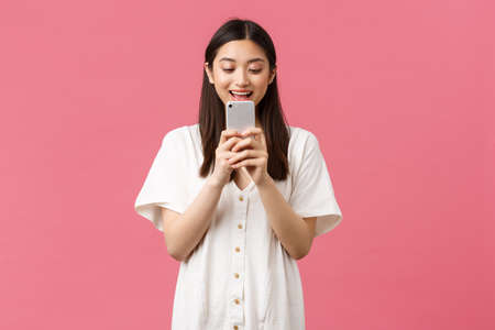 Beauty, emotions and technology concept. Excited asian girl blogger looking at mobile phone with astonished happy face, texting or using application, watching video on smartphone, pink background