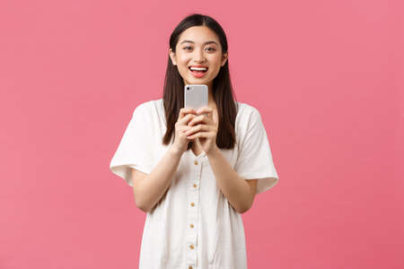 Beauty, people emotions and technology concept. Smiling happy asian female blogger, stylish girl taking photo on smartphone, looking upbeat as photographing, taking picture with mobile phone