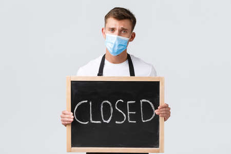 Small retail business owners, covid-19 and social distancing concept. Gloomy and upset salesman, waiter in medical mask inform that cafe closed, showing sign and frowning disappointed