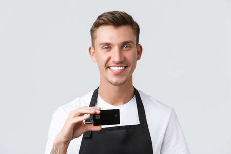 Cafe and restaurants, coffee shop owners and retail concept. Close-up of handsome friendly-looking waiter, salesman smiling broadly and showing credit card, contactless payment option Archivio Fotografico