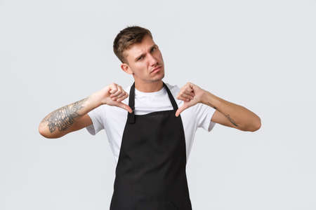Employees, grocery stores and coffee shop concept. Cool and confident serious barista, waiter in black apron pointing at himself with determined expression, care for guests, white background Archivio Fotografico